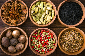 Photo sur Aluminium Spices on a wooden background in bowls, place of copying, seasoning, saffron, cumin, black sesame, cardamom, nutmeg, pink salt, star anise, coriander