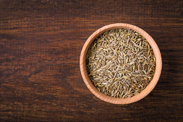 Cumin, zira, seeds in a cup on a wooden background, seasoning, spice