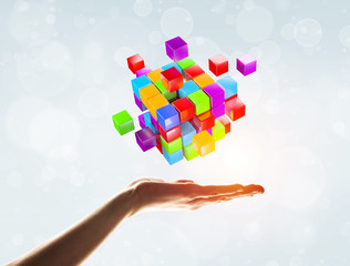 Cube color figure in male palm as symbol for integration. 3D rendering