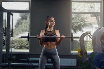 Hot young girl in gym crouching with barbell, against gym equipment.