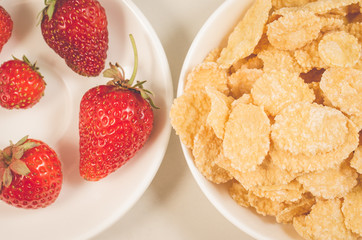 healthy concept with strawberry and flakes/healthy concept: strawberry and flakes in white bowls closeup. Top view