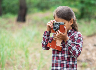 Young photographer. Small girl with camera.