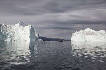 Foto op Canvas Poolcirkel rubber dinghy cruising in front of massive Icebergs floating in the fjord scoresby sund, east Greenland