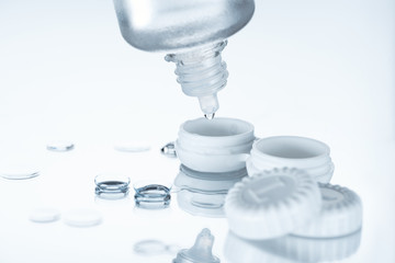 close up view of contact lenses and its storage equipment on white backdrop