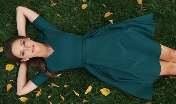 carefree pretty woman is lying on green grass