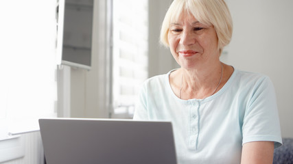 Elderly senior blond woman working on laptop computer at home. Received good news excited and happy. Remote freelance work on retirement, active modern lifestyle of older people.