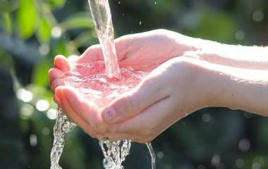 bambina che raccoglie acqua purissima con le mani