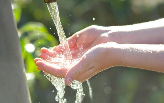 mani di bambina che raccolgono acqua di fonte