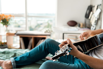 cropped shot of guitarist in jeans playing acoustic guitar on bed at home
