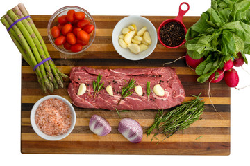 Overhead view of seasoned meat next to vegetables