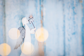 White angel Christmas decoration on blue background with lights