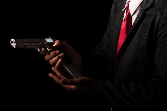 Close up Man changing gun magazines on black background.