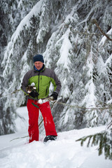 Smiling adventurer with firewood in his hands is walking in snowshoes