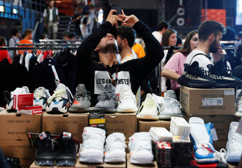 A seller takes a picture at the KICKIT Sneaker e Streetwear Market in Rome