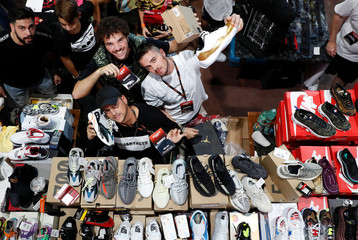 Sellers and clients pose for a picture at the KICKIT Sneaker e Streetwear Market in Rome