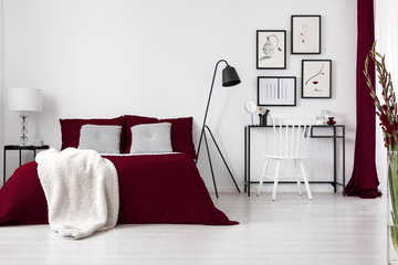 Contrast colors, white, burgundy and black in a modern bedroom interior with bed, dressing table, chair, lamps and graphics. Real photo.