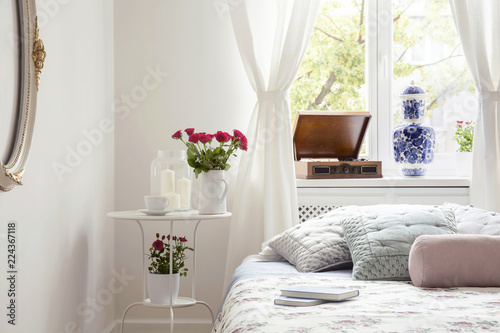 Red roses on table by a bed side in a pastel bedroom interior with a ...