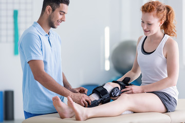 Smiling woman with stiffener on the leg and happy physiotherapist