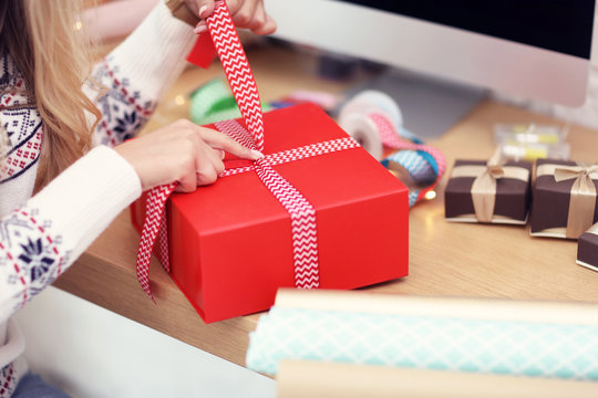 Adult woman at home wrapping Christmas presents
