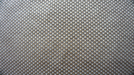Macro image of the detail of a golden place mat with volume squares design for wallpaper or background