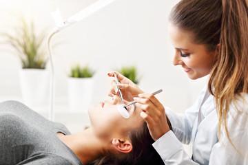 Adult woman having eyelash extension in professional beauty salon