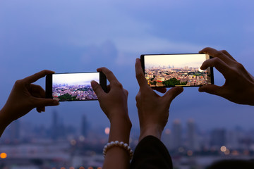 Happy moment of couple takes pictures by cellphone on the rooftop bar in the cityscape with bokeh background