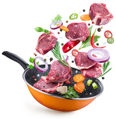 Flying meat steaks and spices over a frying pan. File contains clipping path.
