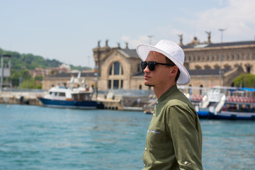 A young guy in a hat, sunglasses stands in the port of Barcelona's at the port customs background, Barcelona, Spain