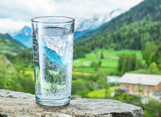 Glass of water on the stone. Blurred snow mountains tops and green forests at the background.