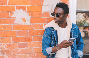 Wall Mural - Fashion african man holds smartphone on city street, brick wall background