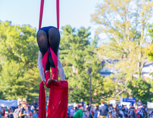 A lady in blue and black fitness outfit is hanging on a red ribbon while attaching red ribbon on her legs