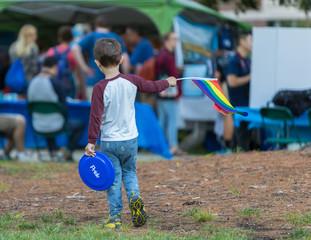 Young boy holding LGBT raimbow flag