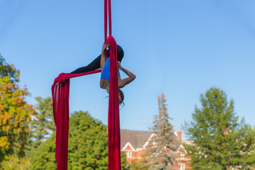 Young Aerial acrobatic dancer viewed against the blue sky