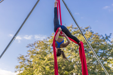 Woman in blue dance is hanging upside down on red ribbon
