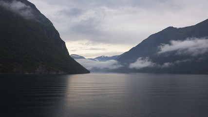 Tranquil view from the water towards the surrounding cliffs of the Geiranger Fjord, Norway, a UNESCO world heritage