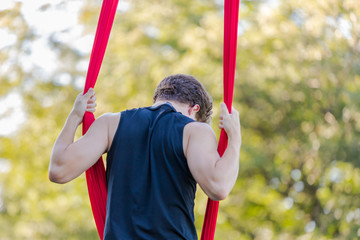 Young male aerial acrobatic dancer is getting ready to climb a red ribbon