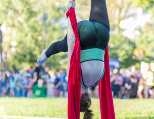 Woman in green and black fitness outfit is hanging upside down on red ribbon