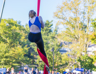 Woman in blue dance outfit climbing a red ribbon