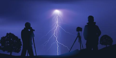 Deux photographes, chasseur d'orages, photographie un éclair la nuit tombée.