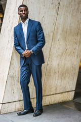 Portrait of Young Handsome African American Businessman in New York, wearing blue suit, white undershirt, leather shoes, wristwatch, standing by column on street outside office, waiting, looking..