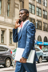 Young African American businessman talking on cell phone, traveling, working in New York, wearing blue suit, carrying laptop computer, walking on street in Manhattan. Cars, buildings on background..