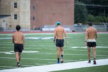 Three men runner are crossing a football stadium