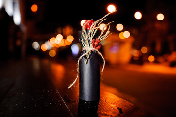 Christmas decorated bottle with ribbon, dried branch and berries in the black paper