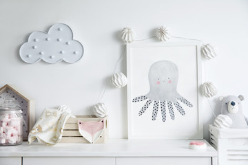 Stylish scandinavian newborn baby room with toys, teddy bears, wooden boxes and cloud. Modern interior with mock up photo frame and childs accessories.