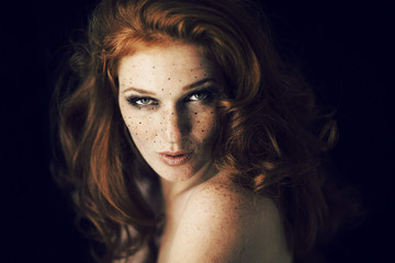 Printed roller blinds Beauty Beautiful young woman with red hair and freckles portrait, beauty shoot on dark background, mysterious dark mood