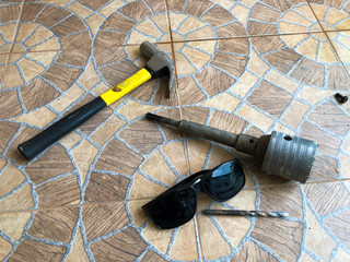 Drilling Equipment Composed of hammers, diggers, dustproof goggles placed on the tile floor.