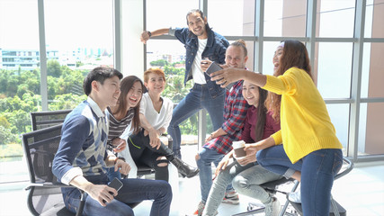 Group of Happy Multi Ethnic in smart casual wear have Fun together  while Talking they're friends  by Smart phone video call at the office