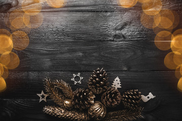 Above view of handmade evergreen tree toys, and golden pines on black wooden background, with space for text writing, greeting card, with light bulbs
