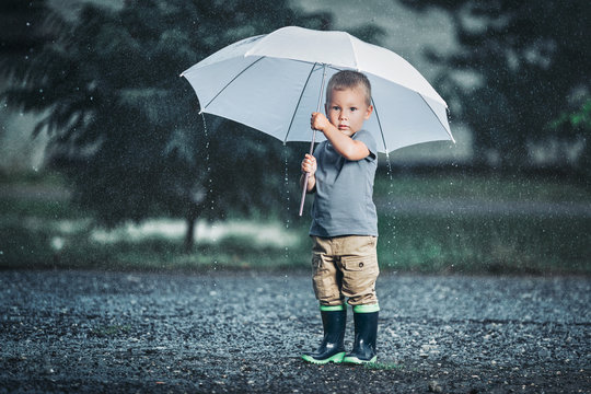 Adorable child holding an umbrella in a rain storm