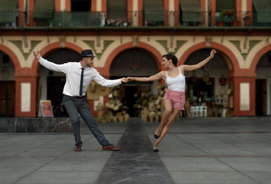 Couple dancing lindy hop happily in and spanish square.